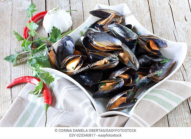 Plate with sauteed mussels decorated with fresh parsley, garlic and red chili pepper