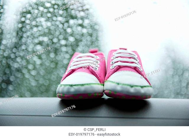 Pink sneakers toddler shoes on the car's dashboard