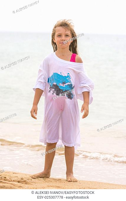 Girl poses funny faces standing on the beach in my father's shirt