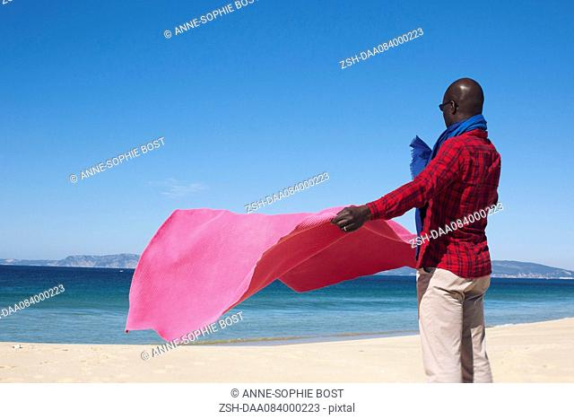 Man at the beach, holding blanket in the breeze