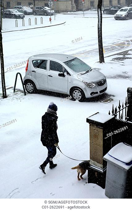 Parked car on pavement, woman walking her dog, snow in town, Strasbourg, Alsace, France
