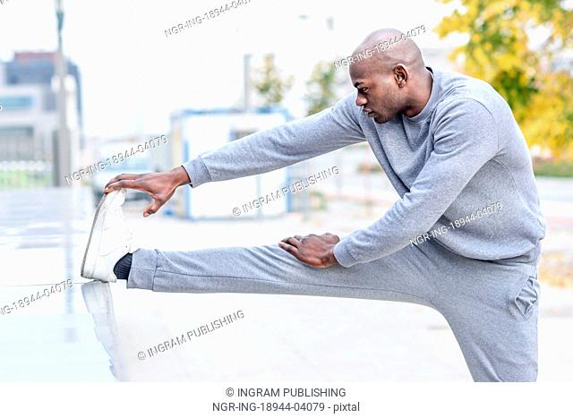 Black man doing stretching before running in urban background. Young male exercising