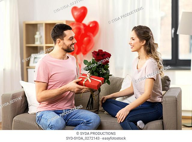 happy man giving woman flowers and present at home