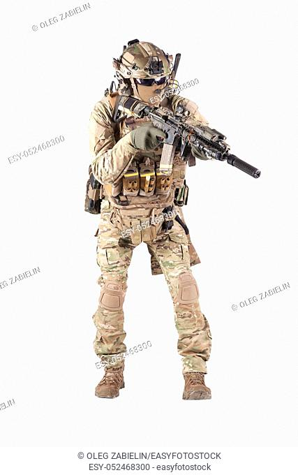 Army infantryman in camouflage uniform, battle helmet, tactical radio headset, extra ammo on load carrier, sneaking, aiming with laser sight on assault rifle...