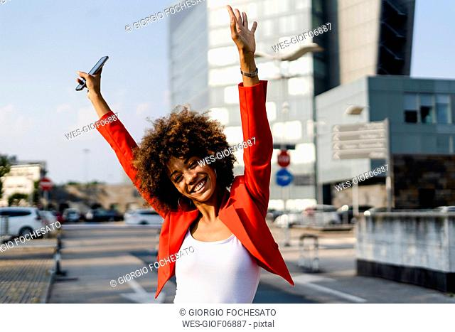 Portrait of happy young woman with smartphone wearing fashionable red suit jacket