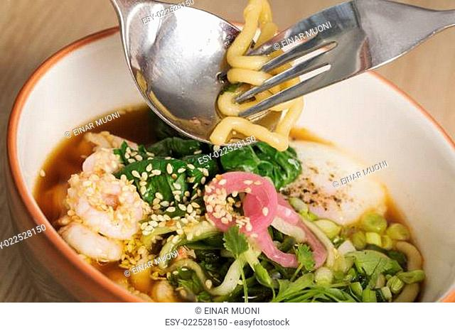Bowl with broth, shrimp and fesh vegetables