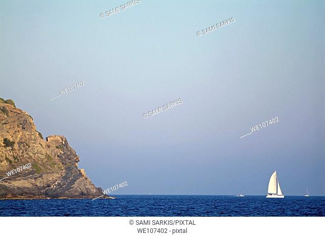 Rocky cliffs and sailboat navigating the waters of the Mediterranean Sea at sunset, Giens, France