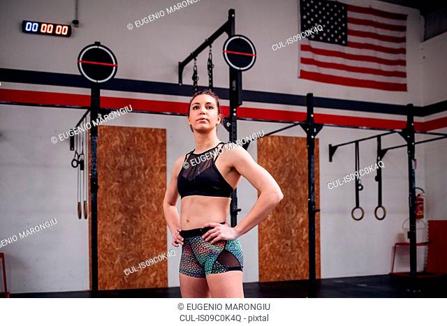 Young woman training, standing in gym with hands on hips
