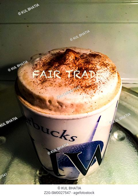 A cup of steaming hot coffee, the words fair trade slpelled out in the froth