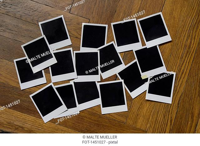 Blank instant camera prints on wooden table