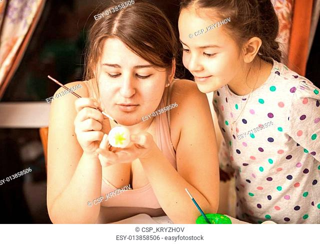 Portrait of mother showing daughter how to paint eggs