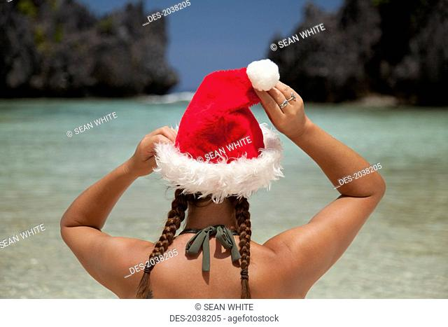 A Woman Tourist Wears A Santa Hat And Bikini On Tropical Matinloc Island Near El Nido And Corong Corong, Bacuit Archipelago On Palawan Philippines