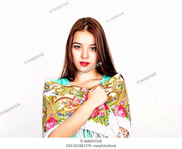 beautiful young woman dressed in a red dress and colored scarf posing in studio