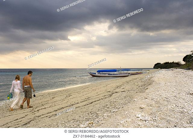 Scenic Landscape. Sunset at Gili Meno Island. Lombok, Indonesia. Some tourists walking along the beach in the western part of the island