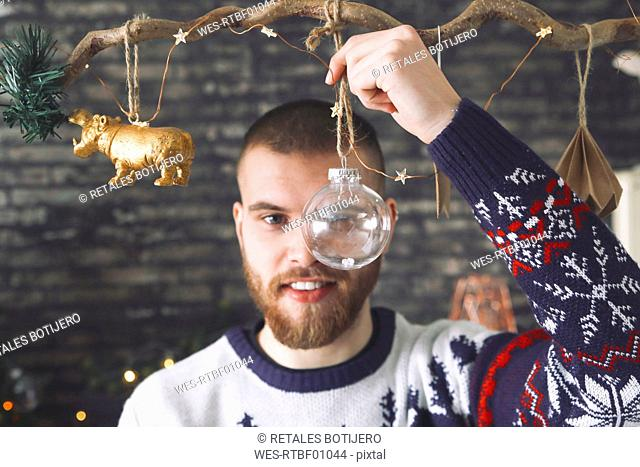 Portrait of man looking through transparent Christmas bauble