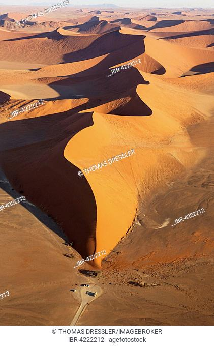 The famous Dune 45 with adjoining car park, camel thorn trees (Acacia erioloba) at the base of the dune, in the evening, aerial view, Namib Desert