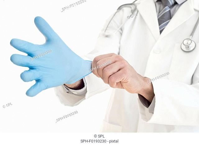 Male doctor putting on blue latex glove