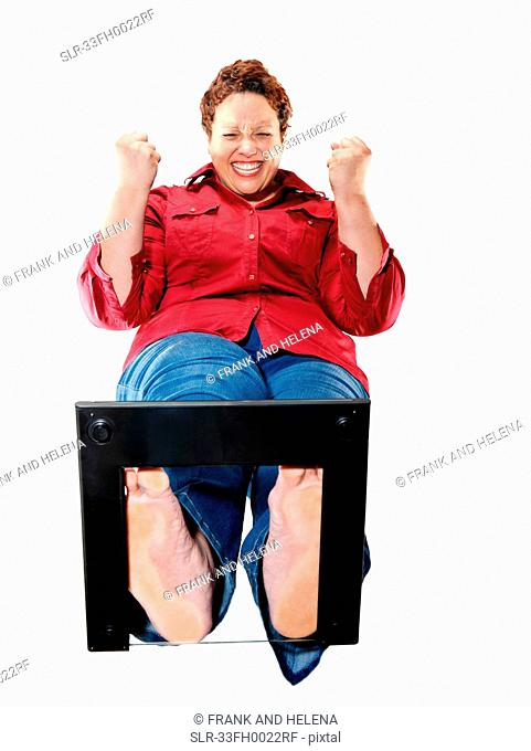 Large woman cheering on scales