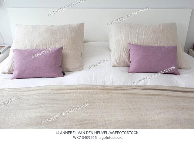 made up bedding in modern comfortable bedroom with clean white bedsheet and pillow with light, clean and clear cozy bed in bedroom with warm light concept