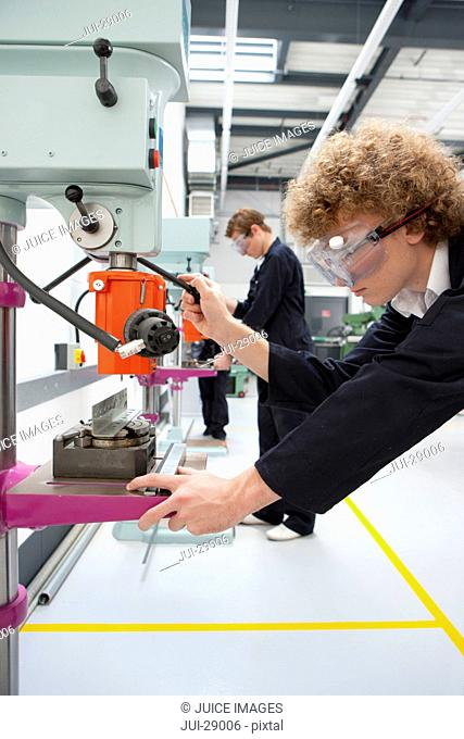 Serious students using drill in vocational school