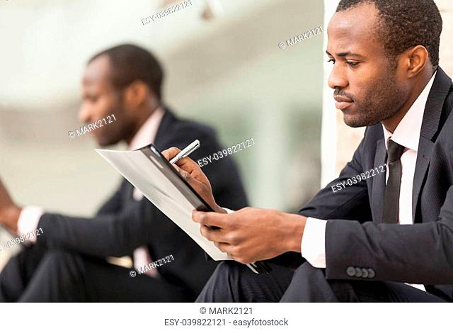 Businessman sits and work with document