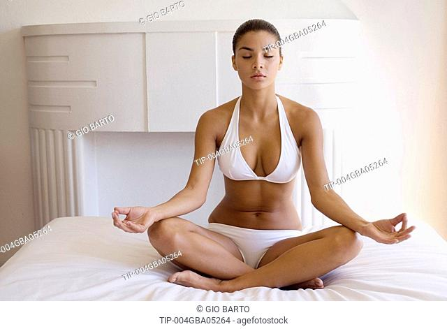 Woman sitting on bed doing yoga