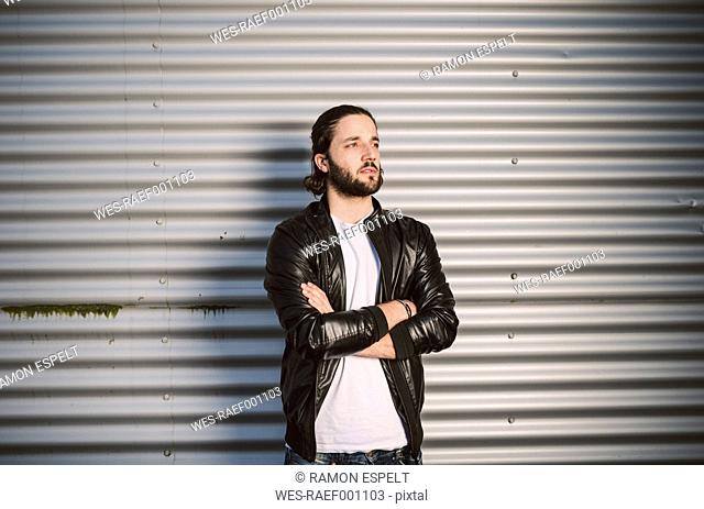 Portrait of young man at corrugated iron wall