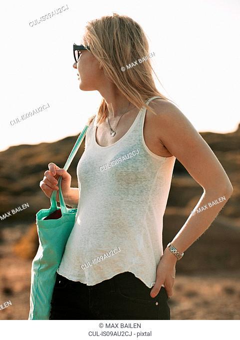 Mid adult woman looking over her shoulder on beach, Menorca, Balearic islands, Spain
