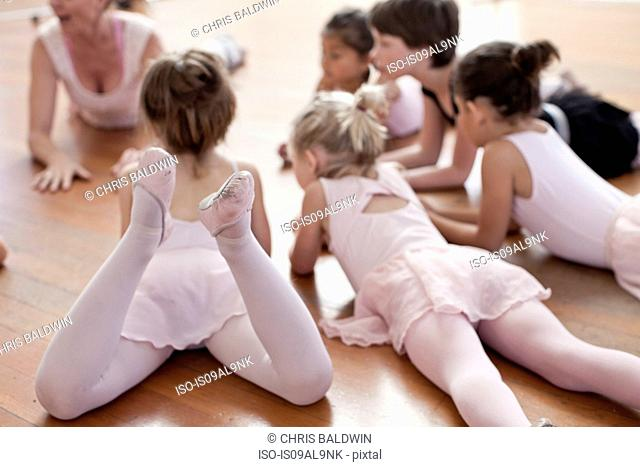 Children lying on floor practicing ballet in ballet school