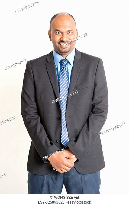 Friendly Indian businessman in formal suit looking at camera, standing on plain background