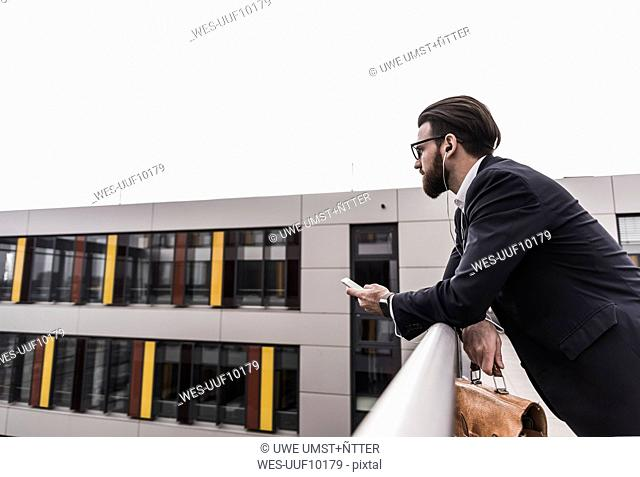 Businessman standing in office building, using smart phone