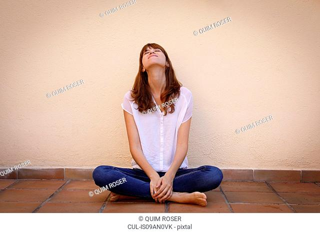 Portrait of mid adult woman in yoga pose on kitchen floor