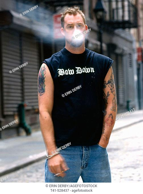 A young man smoking in the downtown streets of Manhattan. He is smoking Marlboro Reds and his tattoos are of pin-up girls. His shirt says 'bow down'