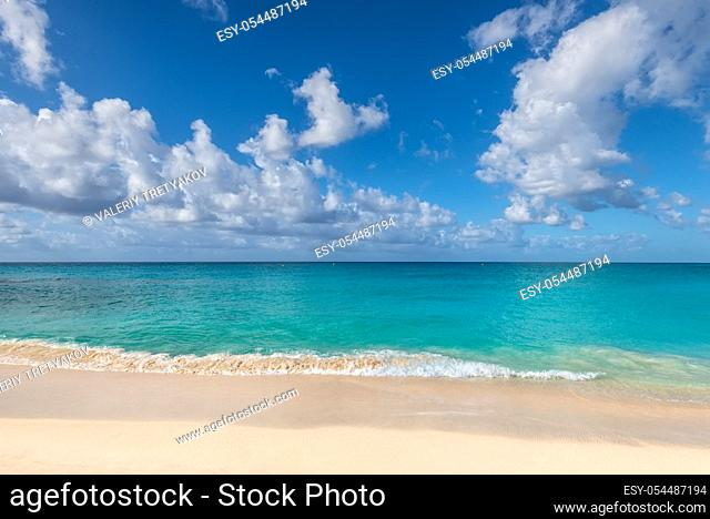 Beautiful marine view on tropical caribbean beach with white sand and turquoise water under blue sky and clouds at sunny day as natural background