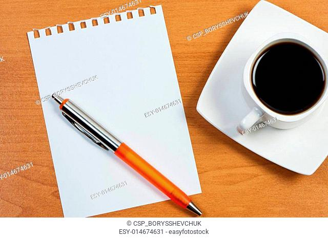 Worksheet with pen and coffee on table