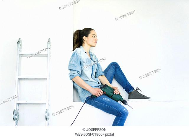 Woman sitting in a niche at ladder holding electric drill