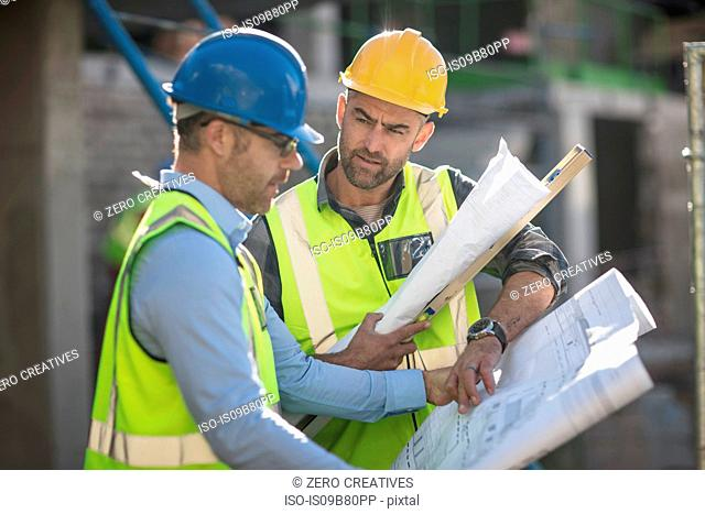 Project manager and construction worker looking at plans
