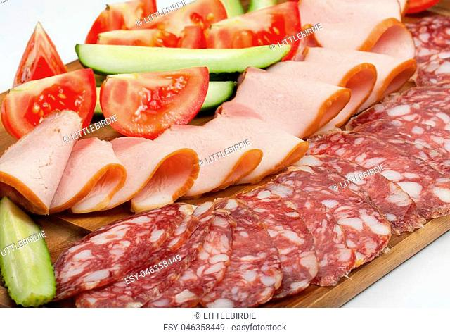 Sliced dry sausages and meat products, cured meat, bacon, with fresh cucumber, tomatoes slices on a wood board