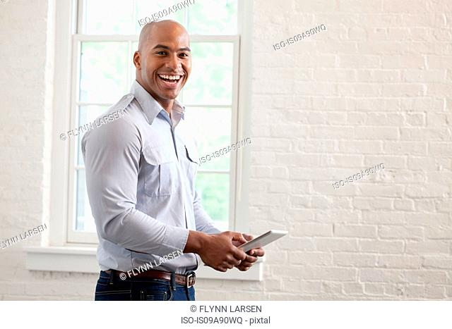 Mid adult office worker holding digital tablet and smiling, portrait