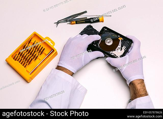 Hands of a technician with gloves repairing a hard drive. Technology maintenance concept