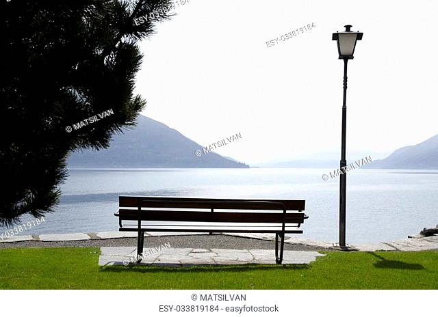 Bench and street lamp on a foggy lakefront with mountain