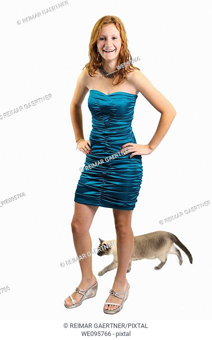 Cut out of teenage girl laughing while a siamese cat walks behind her