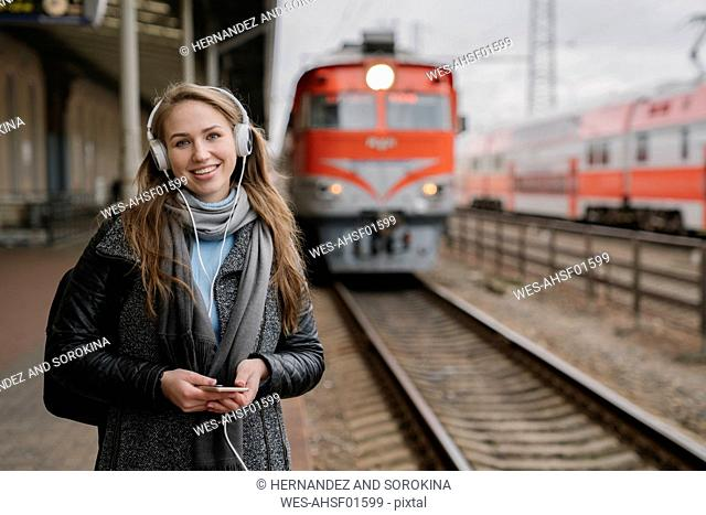 Portrait of happy woman standing on platform using smartphone and headphones, Vilnius, Lithuania