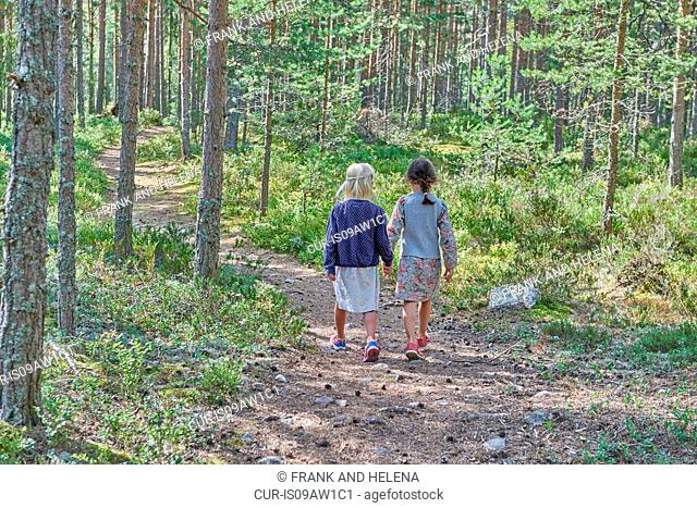 Rear view of two girls wearing retro clothes walking in forest