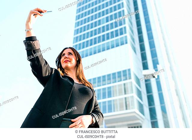Young woman taking smartphone selfie in front of skyscraper, low angle view, Turin, Piemonte, Italy