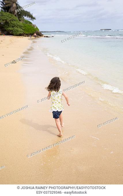Young girl running down the beach while on vacation to Oahu Hawaii