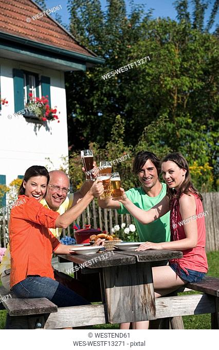 Germany, Bavaria, Friends drinking beer in the garden, clinking glasses