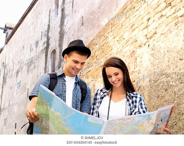 Tourists exploring the map on old baroque street