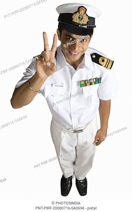 Portrait of a navy officer showing a victory sign