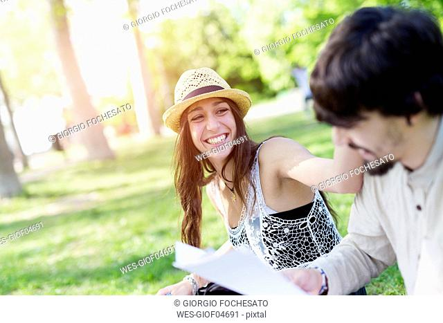 Portrait of laughing young woman having fun in a park with her fellow student